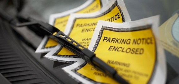 Image of a row of parking notices under a windshield wiper for a blog on top 5 New York driving laws people break